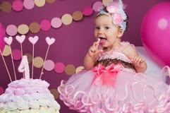 Portret rozochocona urodzinowa dziewczyna z pierwszy tortem troszkę Jeść pierwszy tort Roztrzaskanie tort Obraz Stock