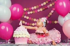 Portret rozochocona urodzinowa dziewczyna z pierwszy tortem troszkę Jeść pierwszy tort Roztrzaskanie tort Obrazy Royalty Free