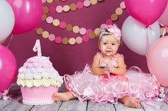 Portret rozochocona urodzinowa dziewczyna z pierwszy tortem troszkę Jeść pierwszy tort Roztrzaskanie tort Zdjęcia Stock