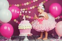 Portret rozochocona urodzinowa dziewczyna z pierwszy tortem troszkę Jeść pierwszy tort Roztrzaskanie tort Fotografia Royalty Free