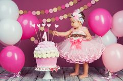 Portret rozochocona urodzinowa dziewczyna z pierwszy tortem troszkę Jeść pierwszy tort Roztrzaskanie tort Obrazy Stock