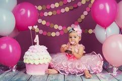 Portret rozochocona urodzinowa dziewczyna z pierwszy tortem troszkę Jeść pierwszy tort Roztrzaskanie tort Obraz Royalty Free