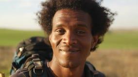 Portret rozochocony amerykanina afrykańskiego pochodzenia młody człowiek z Wycieczkować plecaka Patrzeje kamerę i ono uśmiecha si zdjęcie wideo