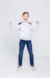 Portret rozochocony chłopiec odświętności zwycięstwo przy pracownianym tłem Fotografia Stock