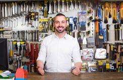 Portret rozochocony mężczyzna przy gotówkowym biurkiem pracuje w artykuły s Obraz Stock