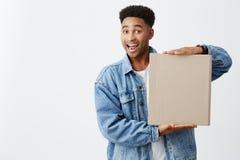 Portret rozochocony młody śmieszny skinned mężczyzna z afro fryzurą w białej koszulce pod drelichowym kurtki mieniem obraz stock