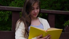 Portret rozochocony nastoletniej dziewczyny czytelniczej książki obsiadanie na ławce w lesie w wiośnie, studiowanie plenerowy Hd  zdjęcie wideo