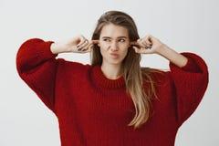 Portret rozpraszająca uwagę niewygodna powabna caucasian dziewczyna w luźnym pulowerze, nakrywkowi ucho z palcami wskazującymi, p obrazy stock