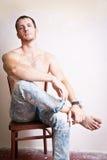 Portret rozważny atrakcyjny mężczyzna obsiadanie na krześle zdjęcie stock