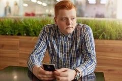 Portret rozważny nastolatek jest ubranym sprawdzać koszulowego mienie telefonu komórkowego obsiadanie przy drewnianego stół ag z  Obraz Stock
