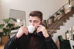 Portret ruchliwie mężczyzna pije kawę od filiżanki i opowiada na telefonie w wygodnej kawiarni obraz stock