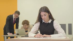 Portret ruchliwie młoda kobieta pisze na papierze w przedpolu w biurze w formalnej odzieży podczas gdy jej samiec i zbiory