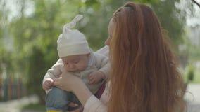 Portret rudzielec śliczna młoda piękna matka trzyma uroczego dziecka w ona i opowiada on w wiosna słonecznym dniu ręki zdjęcie wideo