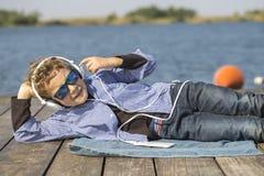 Portret słodka chłopiec z okularami przeciwsłonecznymi i hełmofonami troszkę obraz stock