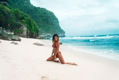 Portret seksowna garbnikująca dziewczyna na plaży Wspaniały model z obcisłą sport postacią w czerwonym bikini fotografia royalty free