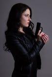 Portret seksowna kobieta w czerni z pistoletem nad popielatym Obrazy Stock