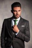 Portret seksowny młody człowiek koryguje jego w smokingu krawat Zdjęcie Royalty Free
