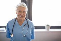 Portret senior lekarki pozycja przeciw okno Fotografia Stock