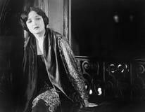 Portret siedzi blisko okno przy nocą kobieta (Wszystkie persons przedstawiający no są długiego utrzymania i żadny nieruchomość is Fotografia Royalty Free