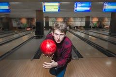 Portret sikający młody człowiek z kręgle piłką w jego ręki Młody człowiek rzuca kręgle piłkę zbliżamy się do kręgli balowe gry sz Obrazy Stock