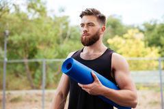 Portret skoncentrowana brodata sporta mężczyzna mienia joga mata obrazy stock