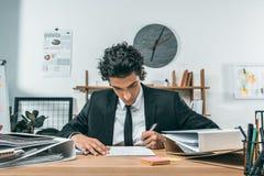 portret skoncentrowany biznesmena writing pracy plan przy miejscem pracy zdjęcia royalty free