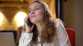 Portret skoncentrowany młody bizneswoman opowiada na telefonie komórkowym na biurowym tle joyfully obraz stock