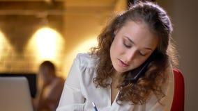 Portret skoncentrowany młody bizneswoman pisze i opowiada na telefonie komórkowym na biurowym tle zdjęcie stock