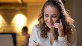 Portret skoncentrowany młody bizneswoman pisze joyfully i opowiada na telefonie komórkowym na biurowym tle obrazy royalty free