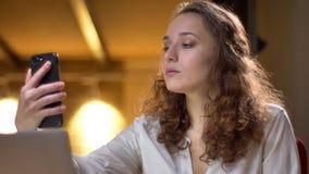 Portret skoncentrowany młody bizneswoman robi fotografiom na biurowym tle używać smartphone obrazy stock