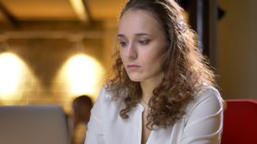 Portret skoncentrowany młody bizneswomanu dopatrywanie w laptop na biurowym tle obrazy stock