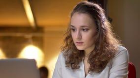 Portret skoncentrowany młody bizneswomanu dopatrywanie w laptop z szokiem na biurowym tle zdjęcia stock