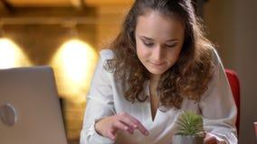 Portret skoncentrowany młody bizneswomanu obsiadanie pisać na maszynie na smartphone na biurowym tle obrazy royalty free