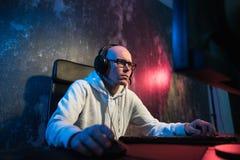 Portret skoncentrowany młody człowiek w szkłach i słuchawki w ciemnym pokoju bawić się online grę komputerową lub współzawodniczy obraz stock