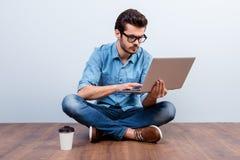 Portret skoncentrowany młody poważny mężczyzna pisać na maszynie na jego laptopie, fotografia stock