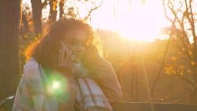 Portret skoncentrowany z włosami caucasian dziewczyny obsiadanie na ławce i opowiadać na telefonie komórkowym w pogodnym jesienny zdjęcie royalty free