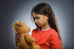 Portret smutna lub nieszczęśliwa dziewczyna bawić się z misiem odizolowywającym na szarość fotografia royalty free