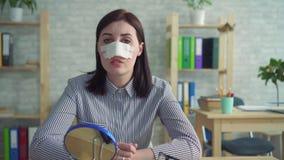 Portret smutna młoda kobieta po tym jak chirurgia plastyczna patrzeje z bandażem na jej twarzy w lustrze zdjęcie wideo