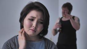 Portret smutna przygnębiona Azjatycka dziewczyna, pijący mąż w tle przysięga, kłóci się, koliduje, spojrzenia przy kamerą zbiory wideo