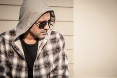 Portret smutny mężczyzna siedzi blisko domu w okularach przeciwsłonecznych Obraz Stock