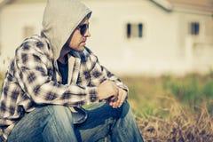 Portret smutny mężczyzna siedzi blisko domu w okularach przeciwsłonecznych Zdjęcie Royalty Free
