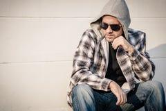 Portret smutny mężczyzna siedzi blisko domu w okularach przeciwsłonecznych Obraz Royalty Free