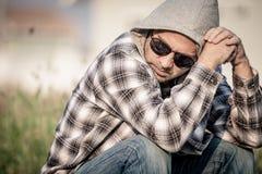 Portret smutny mężczyzna siedzi blisko domu w okularach przeciwsłonecznych Obrazy Stock