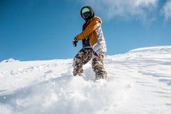 Portret snowboarder w sportswear pozyci na śnieżnym wzgórzu Zdjęcia Royalty Free
