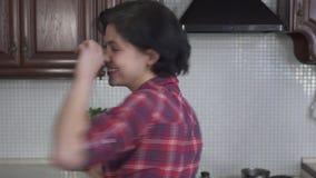 Portret speels meisje die rond met avocado in de keuken voor de gek houden Het lachende vrolijke meisje zet avacado op zijn ogen  stock video