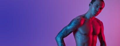 Portret sporta napadu mężczyzna z tatuować rękami Mięśniowa naga półpostać na różowym błękitnym tle fotografia stock