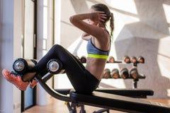 Portret sportowa kobieta robi ćwiczący abdominals opracowywał lying on the beach w gym przy luksusowym hotelem przy latem Zdjęcia Stock