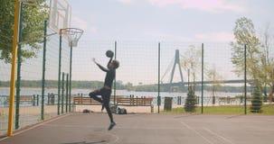 Portret sporty atrakcyjnego amerykanin afrykańskiego pochodzenia męski gracz koszykówki rzuca piłkę w obręcz i świętuje na zbiory