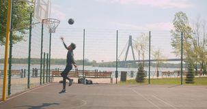 Portret sporty atrakcyjnego amerykanin afrykańskiego pochodzenia męski gracz koszykówki rzuca piłkę w obręcz na sądzie w zbiory wideo