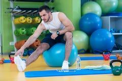 Portret sprawność fizyczna mężczyzna robi rozciąganiu ćwiczy przy gym fotografia stock